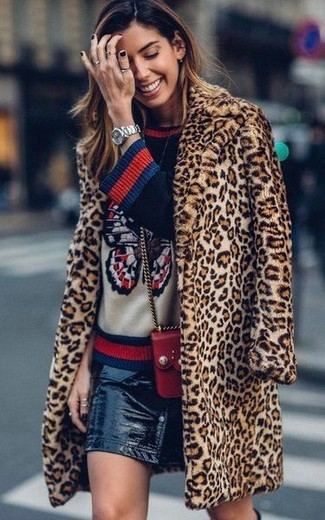 Cómo combinar: bolso bandolera de cuero rojo, falda con botones de cuero negra, jersey con cuello circular estampado azul marino, abrigo de piel de leopardo marrón claro