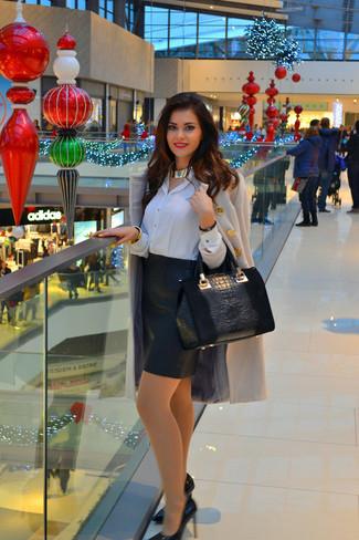 Cómo combinar: zapatos de tacón de cuero negros, falda lápiz de cuero negra, camisa de vestir de seda blanca, abrigo blanco
