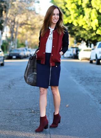 Cómo combinar: botines de ante burdeos, falda lápiz azul marino, camiseta con cuello circular estampada en blanco y negro, chaqueta varsity burdeos