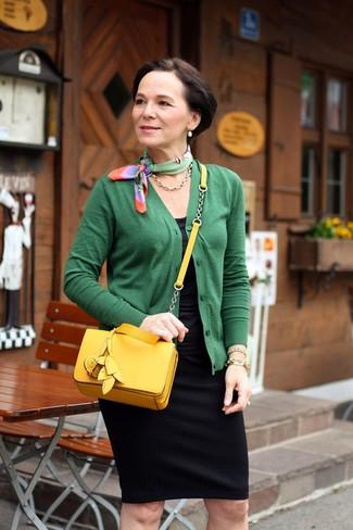 Moda para mujeres de 50 años: Haz de un cárdigan verde y una falda lápiz negra tu atuendo para lograr un look de vestir pero no muy formal.