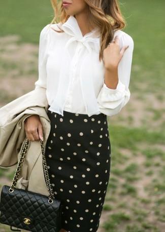 Cómo combinar: bolso bandolera de cuero acolchado negro, falda lápiz a lunares en negro y blanco, blusa de botones blanca, gabardina en beige