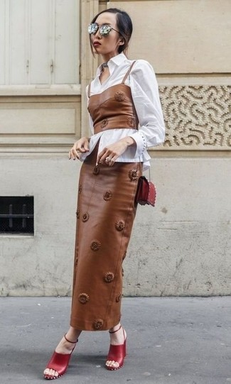 Cómo combinar: sandalias de tacón de cuero rojas, falda larga de cuero marrón, corsé de cuero marrón, camisa de vestir blanca