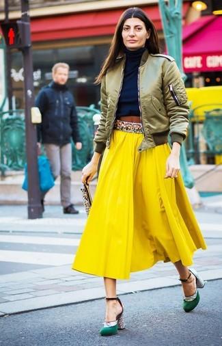 Cómo combinar: zapatos de tacón de satén verdes, falda midi plisada amarilla, jersey de cuello alto azul marino, cazadora de aviador verde oliva