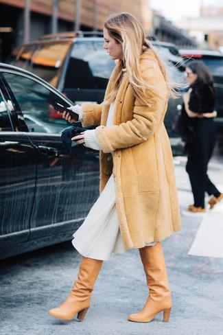 Cómo combinar: botas de caña alta de cuero marrón claro, falda midi de lana blanca, jersey oversized blanco, abrigo de piel de oveja marrón claro