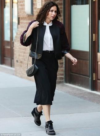 Cómo combinar: zapatillas con cuña de ante negras, falda midi negra, camisa de vestir de seda blanca, chaqueta motera de lana negra
