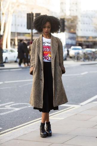 Cómo combinar: botines con cordones de cuero gruesos negros, falda midi plisada negra, camiseta con cuello circular estampada blanca, abrigo marrón