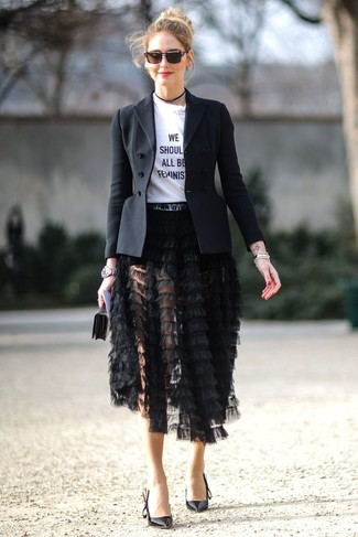 Cómo combinar: zapatos de tacón de cuero negros, falda midi сon flecos negra, camiseta con cuello circular estampada en blanco y negro, blazer negro