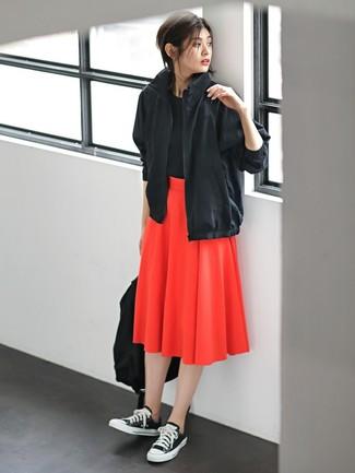 Cómo combinar: tenis de lona en negro y blanco, falda midi plisada roja, camiseta con cuello circular negra, chubasquero negro