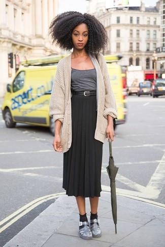 Cómo combinar: sandalias planas de cuero plateadas, falda midi plisada negra, camiseta sin manga en gris oscuro, cárdigan de punto en beige