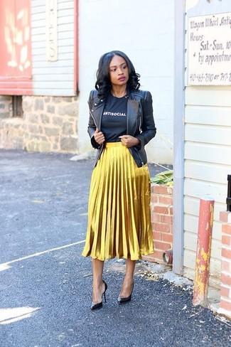 Cómo combinar: zapatos de tacón de cuero negros, falda midi plisada dorada, camiseta con cuello circular estampada en negro y blanco, chaqueta motera de cuero negra