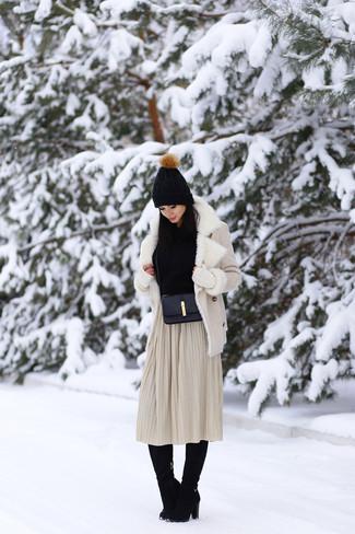 Cómo combinar: botas de caña alta de ante negras, falda midi plisada en beige, jersey con cuello vuelto holgado negro, chaqueta de piel de oveja en beige