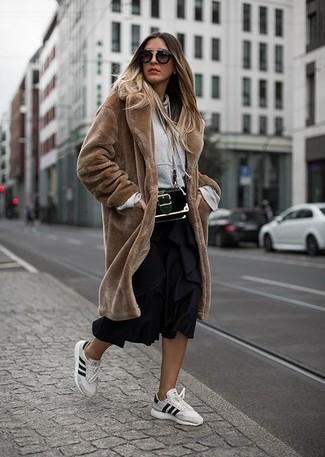 Cómo combinar: tenis de cuero blancos, falda midi plisada negra, sudadera con capucha gris, abrigo de piel marrón