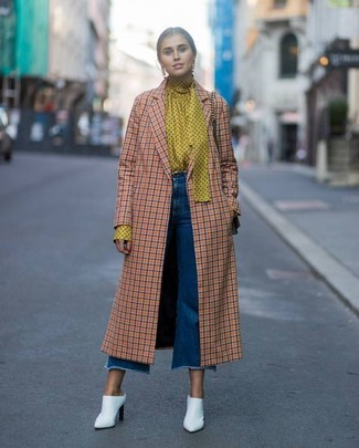 Cómo combinar: chinelas de cuero blancas, falda pantalón vaquera azul, blusa de manga larga a lunares amarilla, abrigo a cuadros naranja