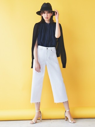 Cómo combinar: sandalias de tacón de cuero plateadas, falda pantalón vaquera blanca, camisa sin mangas azul marino, cárdigan negro