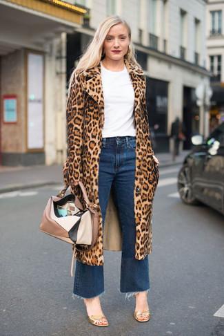 Cómo combinar: sandalias de tacón de cuero doradas, falda pantalón vaquera azul, camiseta con cuello circular blanca, abrigo de piel de leopardo marrón claro