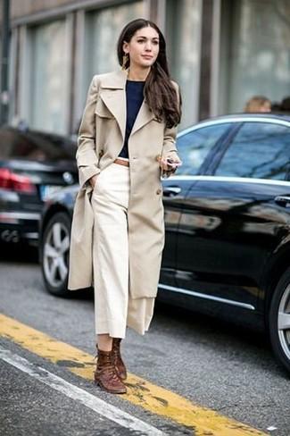 Cómo combinar: botas planas con cordones de cuero marrónes, falda pantalón blanca, camiseta con cuello circular negra, gabardina en beige