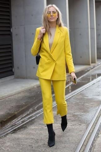Combinar una camiseta de manga larga en beige: Haz de una camiseta de manga larga en beige y una falda pantalón amarilla tu atuendo y te verás como todo un bombón. Este atuendo se complementa perfectamente con botines de elástico negros.