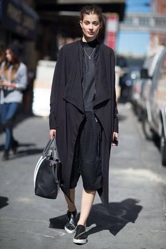 Cómo combinar: zapatillas slip-on de cuero negras, falda pantalón negra, camiseta de manga larga en gris oscuro, gabardina negra