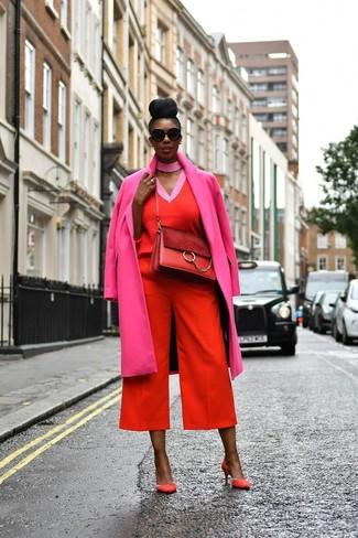 Cómo combinar: zapatos de tacón de ante rojos, falda pantalón roja, jersey de pico rojo, abrigo rosa