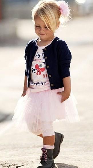 Cómo combinar: botas negras, falda rosada, camiseta estampada rosada, cárdigan azul marino