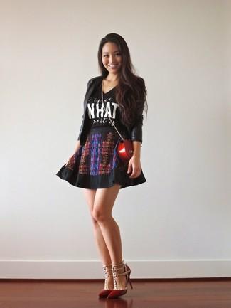 Cómo combinar: zapatos de tacón de cuero rojos, falda skater estampada negra, camiseta con cuello circular estampada en negro y blanco, blazer de cuero negro