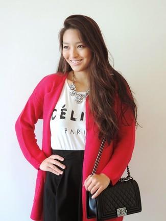 Cómo combinar: bolso bandolera de cuero acolchado negro, falda skater negra, camiseta con cuello circular estampada en blanco y negro, cárdigan abierto rosa