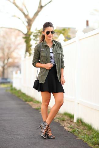 Cómo combinar: sandalias de tacón de cuero con print de serpiente grises, falda skater negra, camiseta con cuello circular estampada en blanco y negro, chaqueta militar verde oliva