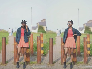 Cómo combinar: botas planas con cordones de cuero negras, falda skater naranja, camiseta sin manga roja, chaquetón azul marino