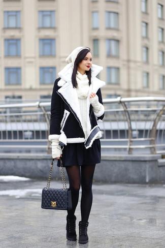 Cómo combinar: botas planas con cordones de ante negras, falda skater negra, jersey con cuello circular blanco, chaqueta de piel de oveja en negro y blanco