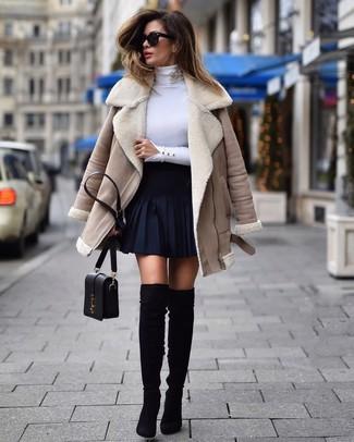 Cómo combinar: botas sobre la rodilla de ante negras, falda skater azul marino, jersey de cuello alto blanco, chaqueta de piel de oveja en beige