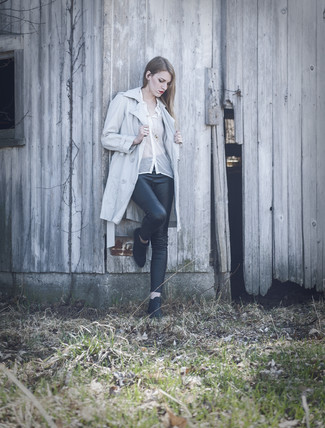 Cómo combinar: gabardina celeste, blusa de botones de gasa blanca, leggings de cuero negros, botines de cuero negros