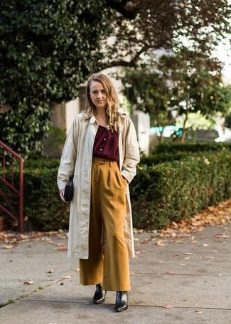Cómo combinar: gabardina en beige, blusa de botones burdeos, pantalones anchos mostaza, botines de cuero negros