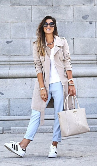 Cómo combinar: gabardina en beige, camiseta con cuello en v blanca, pantalón chino celeste, tenis de cuero en blanco y negro
