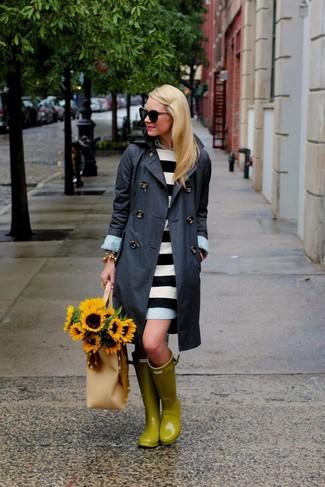 Cómo combinar: gabardina en gris oscuro, vestido casual de rayas horizontales en blanco y negro, botas de lluvia amarillas, bolsa tote de cuero en beige