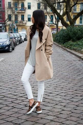 Look de moda: Gabardina Marrón Claro, Camiseta con Cuello Circular de Rayas Horizontales Blanca, Vaqueros Pitillo Blancos, Zapatillas Slip-on de Leopardo Marrónes