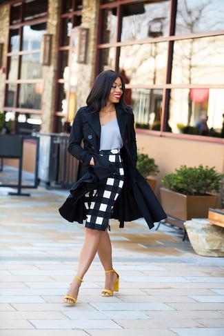 Cómo combinar: gabardina negra, camiseta sin manga de seda gris, falda lápiz a cuadros en blanco y negro, sandalias de tacón de cuero amarillas