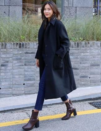 Cómo combinar: gabardina negra, jersey con cuello circular negro, vaqueros pitillo azul marino, botines de cuero en marrón oscuro