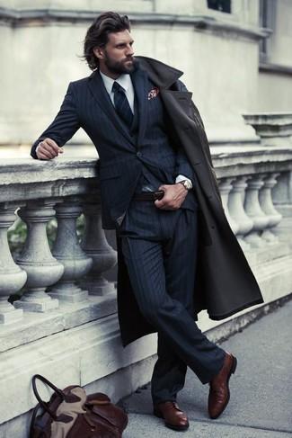 Algo tan simple como optar por una gabardina y un traje de tres piezas de rayas verticales azul marino puede distinguirte de la multitud. Zapatos derby de cuero marrón oscuro contrastarán muy bien con el resto del conjunto.