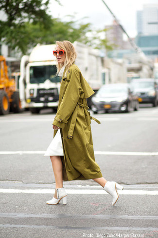 Utiliza una gabardina verde oliva y un vestido midi blanco para cualquier sorpresa que haya en el día. Botines de cuero blancos son una sencilla forma de complementar tu atuendo.