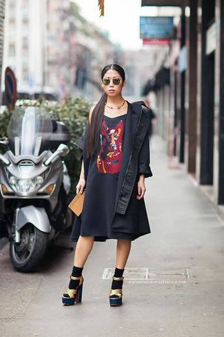 Opta por una gabardina negra y un vestido casual estampado negro para un almuerzo en domingo con amigos. ¿Te sientes valiente? Haz sandalias de tacón de cuero doradas tu calzado.