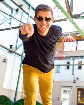 Cómo combinar: gafas de sol en marrón oscuro, pantalón chino mostaza, camisa de manga larga negra