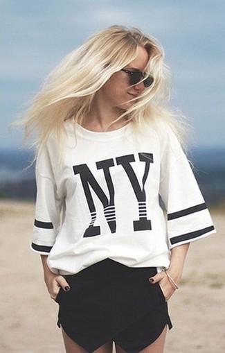 Combinar una camiseta con cuello circular estampada en blanco y negro: Opta por una camiseta con cuello circular estampada en blanco y negro y unos pantalones cortos negros para crear una apariencia elegante y glamurosa.