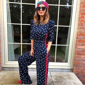 Cómo combinar: cinta para la cabeza en multicolor, gafas de sol negras, zapatos de tacón de ante rojos, mono a lunares azul marino