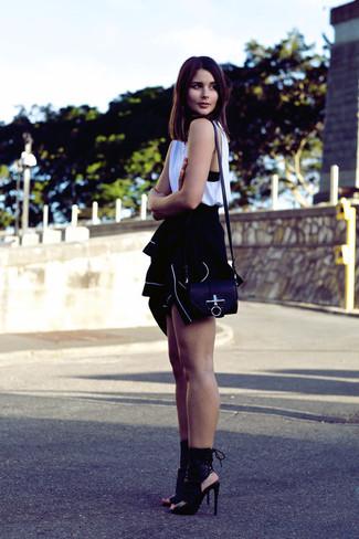 Emparejar un jersey con cremallera negro con una blusa sin mangas blanca es una opción atractiva para el fin de semana. Botines de cuero negros proporcionarán una estética clásica al conjunto.