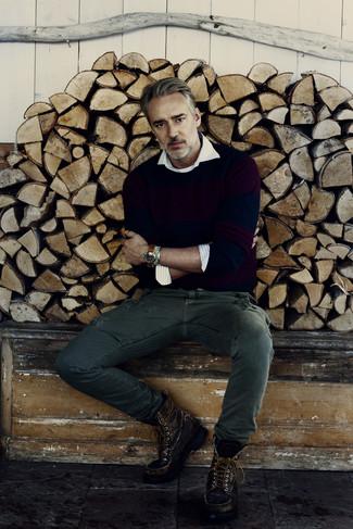 Cómo combinar: jersey con cuello circular azul marino, camisa de manga larga de rayas verticales blanca, pantalón cargo verde oscuro, botas de trabajo de cuero en marrón oscuro