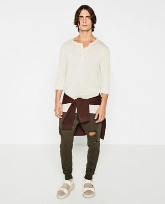 Cómo combinar: jersey con cuello circular burdeos, camiseta henley de manga larga en beige, pantalón de chándal verde oliva, sandalias de cuero blancas
