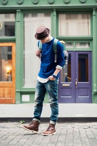 Cómo combinar: jersey con cuello circular azul marino, camisa de manga larga blanca, vaqueros azules, botas casual de cuero marrónes