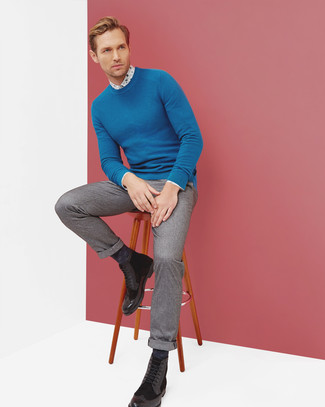 Cómo combinar: jersey con cuello circular azul, camisa de vestir con print de flores blanca, pantalón de vestir de lana gris, botas brogue de cuero negras