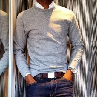 Cómo combinar: jersey con cuello circular gris, camisa de manga larga blanca, vaqueros azul marino, correa de cuero burdeos