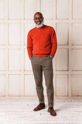 Cómo combinar: jersey con cuello circular naranja, camisa vaquera celeste, pantalón chino marrón, botas safari de ante marrónes